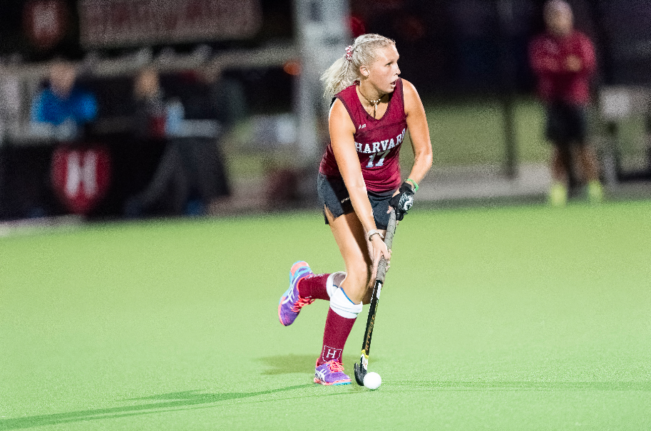 A woman with light blonde hair is playing Field Hockey for Harvard on an artificial pitch. She is wearing a crimson shirt and socks, and a black skirt. Her stick is black.