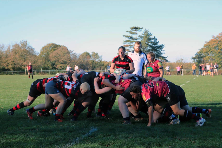Two teams of women's rugby players are scrummaging against each other - Blackheath and Cranbrook. A Blackheath player is about to feed the ball into the scrum.