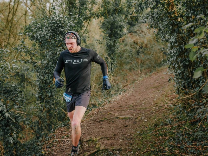 Man listening to a running podcast while running